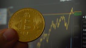 Bitcoin硬币在人的手上在贸易的终端对面的 股票录像