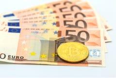 bitcoin符号硬币在钞票50欧元背景的 到达天空的企业概念金黄回归键所有权 库存图片