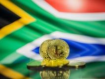 Bitcoin金币和南非背景defocused旗子  真正cryptocurrency概念 免版税库存图片