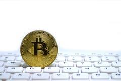 bitcoin金黄符号硬币在白色键盘的 免版税库存图片