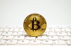 bitcoin金黄符号硬币在白色键盘的 库存图片
