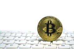 bitcoin金黄符号硬币在白色键盘的 库存照片