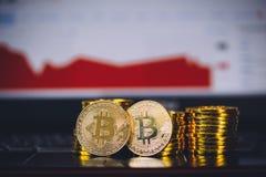 Bitcoin铸造坐在与碰撞和转动红色图表图数字式背景的市场的前面的堆和微不足道的硬币 库存图片