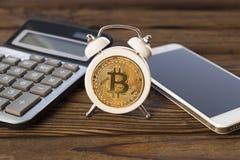 Bitcoin,闹钟,计算器,在木背景的智能手机 库存照片