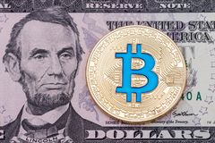 Bitcoin золотого cruptocurrency голубое на предпосылке банкноты доллара Стоковые Фотографии RF