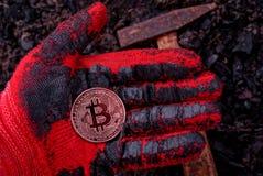 Bitcoin монетки лежит на gloved руке против земли и молотка Стоковые Фото