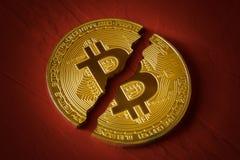 Bitcoin монетки сломленно в половине на красной предпосылке Падение и сброс давления курса секретной валюты, запрета на торговле стоковая фотография