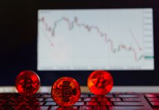 Bitcoin на клавиатуре в красном цвете, на предпосылке нисходящей диаграммы Стоковое фото RF