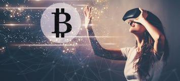 Bitcoin при женщина используя шлемофон виртуальной реальности стоковое изображение