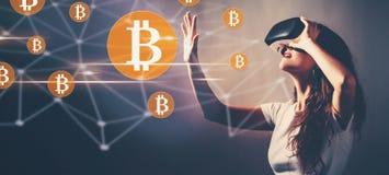 Bitcoin при женщина используя шлемофон виртуальной реальности стоковые фото