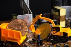 Bitcoin раскопок Backhoe на mainboard положило в тележку стоковые фотографии rf