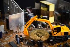 Bitcoin раскопок Backhoe на mainboard стоковые фото