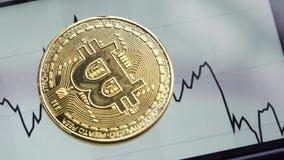 Bitcoin секретный-валюты золота падает на экран с финансовым план-графиком, концом-вверх акции видеоматериалы