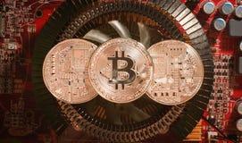 Bitcoin серебряных монет на heatsink видеокарты в красном свете Стоковое Фото