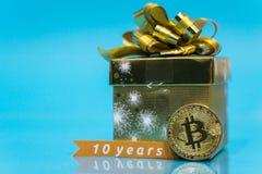 Bitcoin празднуя день рождения, монетка с настоящим моментом дня рождения золотым за им и 10 лет подписывают, с голубым космосом  стоковое изображение rf