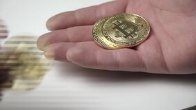 Bitcoin acuña a la mano masculina, el concepto de cryptocurrency de la ganancia almacen de video