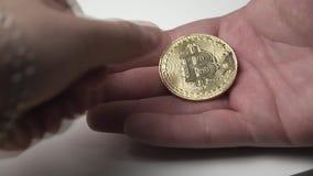 Bitcoin acuña a la mano masculina, el concepto de cryptocurrency de la ganancia almacen de metraje de vídeo