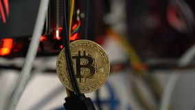 Bitcoin against the background of cables in the rack for crypto-currency mining. Close up stock video