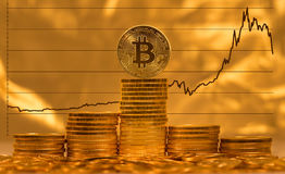 Bitcoin against background of price graph. Single bitcoin on stack of gold coins with graph of price change against US dollar in background Stock Images