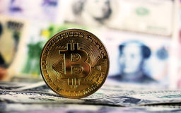 Bitcoin agaisnt of different banknotes. Golden Bitcoin against of different banknotes on background. Cryptocurrency Trading concept Stock Image
