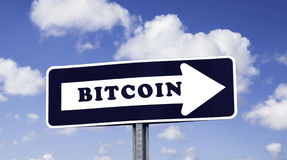 BITCOIN arrow sign. Blue and white street direction arrow sign with description ` BITCOIN `.nBlue background with white clouds.nCryptocurrency and digital royalty free stock photo
