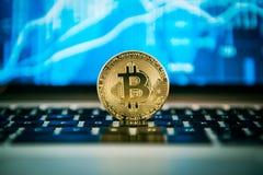Bitcoin auf einem Notizbuch, finacial Diagramm im Hintergrund stockfotografie