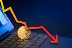 Bitcoin auf Laptoptastatur mit dem Pfeil, der unten zeigt Stockfotografie