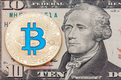 Bitcoin azul del cryptocurrency de oro en backgr del billete de banco de diez dólares fotos de archivo