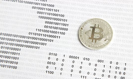 Bitcoin on the background of binary code. Silver bitcoin on the background of binary code stock photography