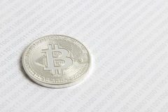 Bitcoin on the background of binary code. Silver bitcoin on the background of binary code royalty free stock photo