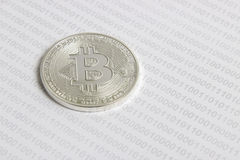 Bitcoin on the background of binary code. Silver bitcoin on the background of binary code royalty free stock photography