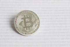 Bitcoin on the background of binary code. Silver bitcoin on the background of binary code royalty free stock photos