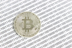 Bitcoin on the background of binary code. Silver bitcoin on the background of binary code stock photo
