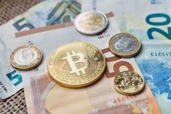 Bitcoin badania lekarskiego moneta i euro monety siedzi na Euro banknotach obraz stock