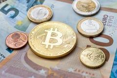 Bitcoin badania lekarskiego moneta i euro monety siedzi na Euro banknotach fotografia royalty free