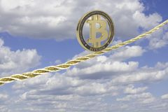 Bitcoin balancing on golden rope Stock Photo