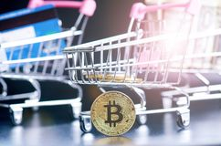 Bitcoin, bank card and money in a trolley on a black background. Concept of shopping and money. Cryptocurrency. Online shopping. V. Irtual currency and business Royalty Free Stock Images