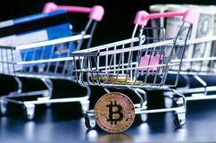 Bitcoin, bank card and money in a trolley on a black background. Concept of shopping and money. Cryptocurrency. Online shopping. V. Irtual currency and business Royalty Free Stock Image