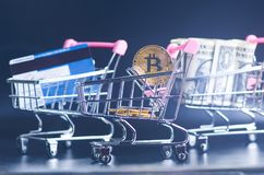 Bitcoin, bank card and money in a trolley on a black background. Concept of shopping and money. Cryptocurrency. Online shopping. V. Irtual currency and business Stock Photos