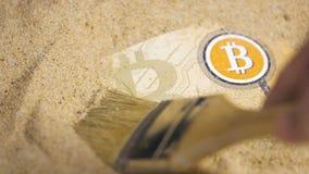 Bitcoin-Banknote gesäubert mit Bürste vom Sand stock footage