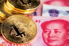 Bitcoin and banknotes of one hundred yuan. Background with crypto bitcoin and China yuan. Bitcoin with Chinese banknotes. Cryptocurrency digital currency close royalty free stock image