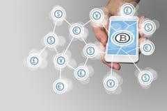 Bitcoin begrepp på grå bakgrund med smartphonen som exemplet för fena-tech Arkivbilder