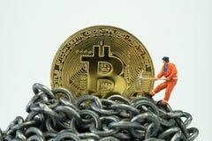 Bitcoin-Bergbaukonzept durch geringe Miniaturarbeitskraft, kleine Minifeige Lizenzfreie Stockfotos