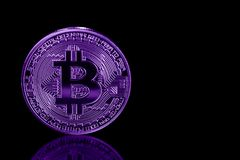 Bitcoin on black background with reflection. Ultraviolet image