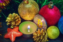 Bitcoin bland julpynt och en stearinljus Royaltyfri Fotografi
