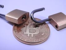 Bitcoin and brass padlocks. Bitcoin and open brass padlocks on gray background Stock Photos