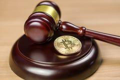 Bitcoin?? BTC隐藏硬币和惊堂木在书桌上 免版税库存照片