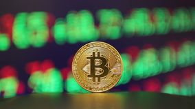 Bitcoin - BTC - Bit Coin. Bitcoin gold coin and defocused chart background stock footage