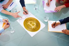 Bitcoin BTC business meeting with hands pointing. To cryptocurrency Stock Photos