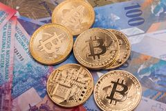 Bitcoin crypto currency coin over swiss francs bank notes Stock Photos